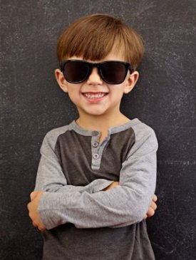 Photo of adorable young happy boy looking at camera with sunglasses. Little kid smiling with his arms crossed against black background.