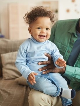 Full length portrait of cute mixed-race baby laughing happily looking at camera while sitting on fathers lap
