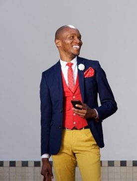 Portrait of happy young african businessman standing outdoors with cellphone